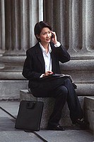 Female executive sitting, using cellular phone