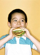 Young boy eating large hamburger, yellow background.