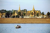 Cambodia, Phnom Penh, Tonle Sap River, Cham fisherman cross river with Royal palace and Silver Pagoda in background.