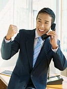 close-up of a businessman smiling while talking on the telephone