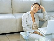businesswoman leaning against a couch in front of a laptop