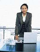 portrait of a businesswoman standing in front of a laptop in an office