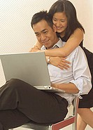 Man using laptop, woman hugging him