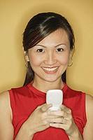 Young woman wearing a red top, holding a mobile phone
