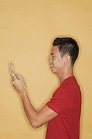 Young man holding mobile phone, profile
