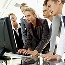 low angle view of five business executives standing in front of a computer monitor