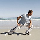 mid adult man exercising on the beach