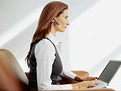 side profile of a businesswoman sitting on a couch and using a laptop