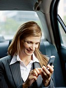 businesswoman using a mobile phone in a car