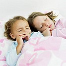 close-up of two girls sleeping on the bed