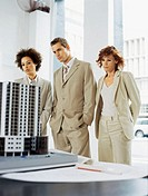 businessman and two businesswomen looking at an architectural model
