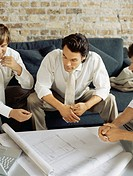 high angle view of three businessmen discussing a blueprint in an office