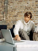 two businessmen sitting in front of a laptop