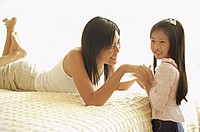 Mother and daughter in bedroom, face to face