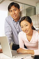 Young couple with laptop, looking at camera