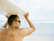 Rear view of a mid adult man holding up a  surfboard