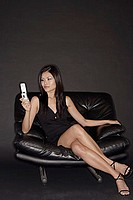 Young woman with mobile phone, sitting on black chair