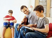 Side profile of two boys and their teacher playing musical instruments