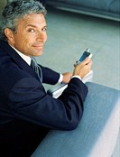 Portrait of a businessman holding a mobile phone, smiling