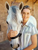 Portrait of a girl hugging a horse and smiling