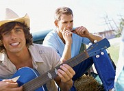 Close-up of a young man playing the guitar and a young man playing harmonica