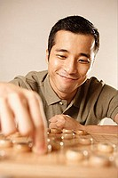 Man playing Chinese chess, smiling