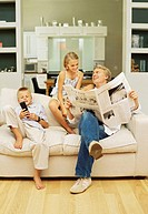 Father sitting on a sofa with his son and daughter reading a newspaper