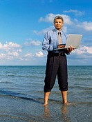 Mature man standing on the beach, holding a laptop