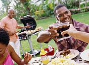 men toasting at a outdoor barbeque