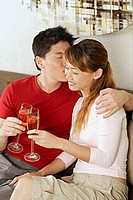 Couple toasting with champagne, man kissing woman on cheek