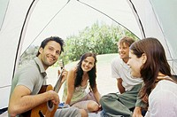 Young man sitting with his friends and playing guitar inside a tent
