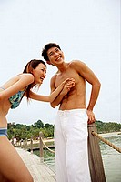 Couple on jetty, holding hands and laughing