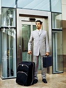 Businessman standing in front of elevator with luggage and briefcase