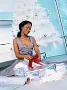 Close up view of a young woman sitting by the Christmas tree wrapping gifts