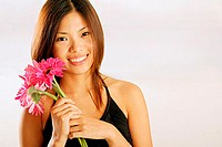 Young woman with bouquet of flowers, smiling at camera