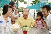 Three generation family celebrating grandfather´s birthday