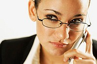 Businesswoman using mobile phone with a serious expression