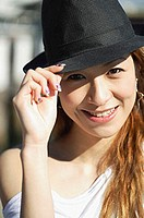 Young woman looking at camera, wearing hat