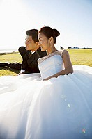 Bride and groom sitting outdoors on grass looking away