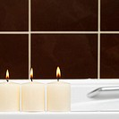 Close-up of three burning candles on side of bathtub