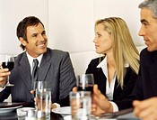 Two businessmen and a businesswoman in a restaurant