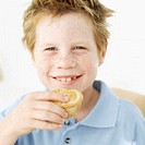 Portrait of a young boy (8-10) holding a muffin