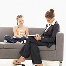 Young businesswoman sitting on a sofa writing and a young girl (8-10) playing with a doll