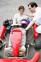 Young woman in go-cart, father crouching down next to her