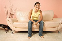 Young woman, sitting on sofa, looking at camera