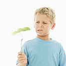 Young boy (8-9) holding a lettuce leaf with a fork