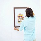 Rear view of a young man adjusting a painting on a wall