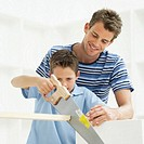 Young man watching a young boy (8-10) cutting a plank of wood with a saw