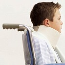 Side profile of a young boy sitting in a wheelchair wearing a neck brace