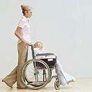 Side profile of a young woman pushing a young girl in a wheelchair